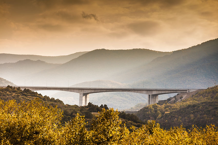 Long bridge with yellow trees in front of it and majestic mountain tops behind