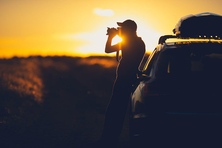 Man leaning on his car and taking a photo of the sunset