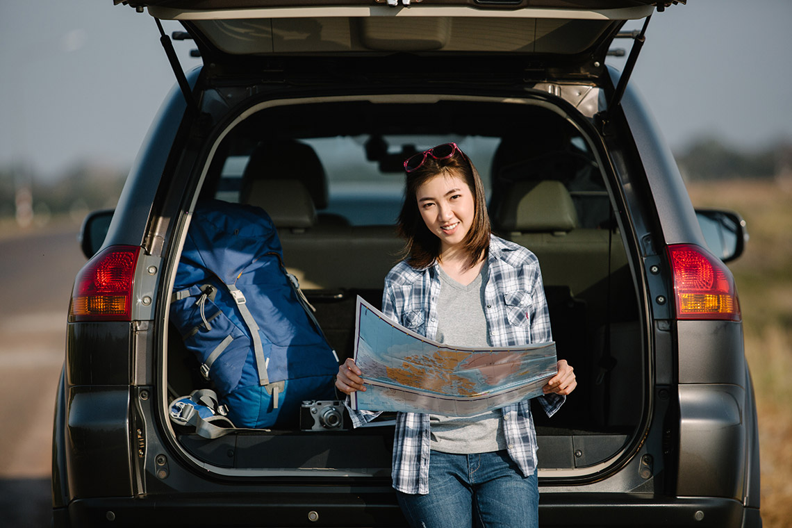 Girl with a map sitting under open tailgate