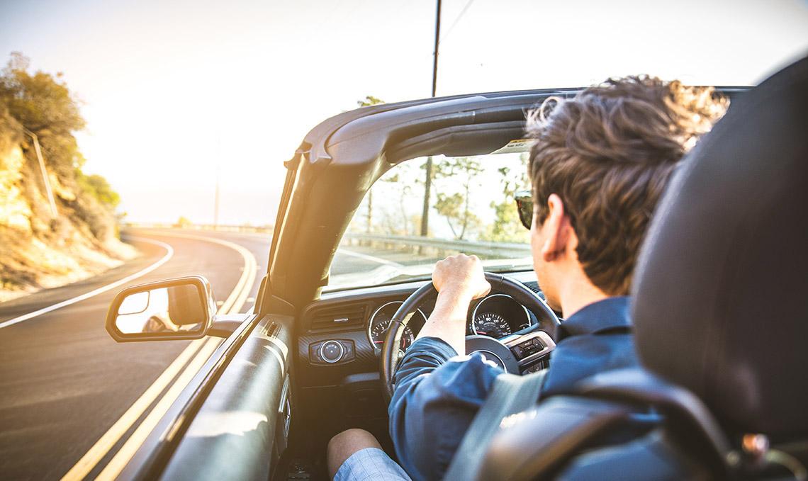 A man driving a Hertz rental car